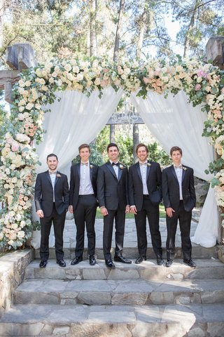 groom-in-tuxedo-with-groomsmen-in-taupe-bow-ties-boutonnieres-ceremony-arch-stone-steps
