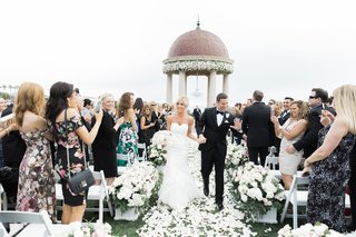 bride-and-groom-hold-hands-walking-up-aisle-friends-clapping-resort-at-pelican-hill-flowers-by-cina