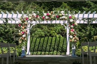wedding-ceremony-arbor-outdoor-venue-pink-white-orange-flowers-greenery