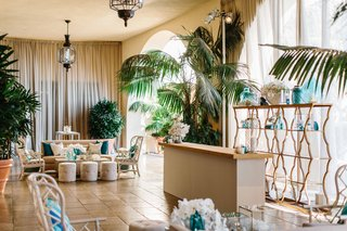 wedding-reception-cocktail-hour-lounge-tropical-beach-theme-with-blue-decor-wicker-chairs-ottomans