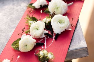 groomsmen-ranunculus-blossom-wedding-boutonniere-styles-on-red-cardboard