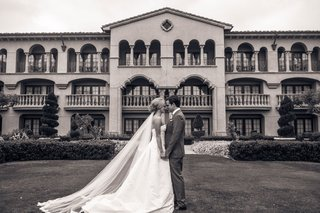 black-and-white-photo-of-bride-and-groom-in-front-of-grand-del-mar-in-san-diego-california-wedding
