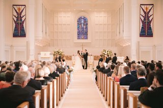 wedding-ceremony-at-traditional-church-with-stained-glass-window-guests-in-pews-christian-ceremony
