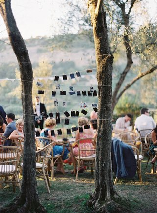 wedding-reception-family-photos-on-string-between-trees-guests-at-outdoor-reception-rattan-chairs