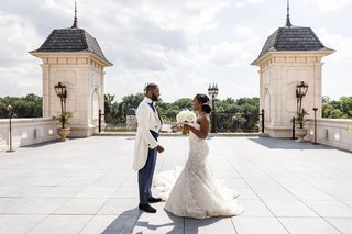 bride-and-groom-first-look-at-the-legacy-castle-outdoor-area-clouds-and-regal-attire