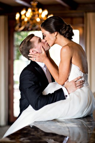 bride-in-reem-acra-groom-in-white-tie-tuxedo-bride-sits-on-counter-to-kiss-groom