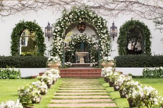 white-flowers-and-greenery-on-arch-of-spanish-colonial-home-at-home-wedding-reception-ideas