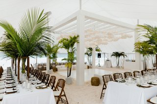 wedding-reception-on-white-sand-beach-bahamas-tropical-decor-green-palms-white-paper-lanterns-decor