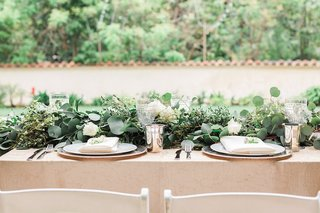 garden-wedding-reception-table-with-greenery-runner-white-roses-golden-tablecloth-silver-tumblers
