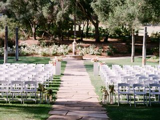 outdoor-wedding-ceremony-with-stone-aisle-and-white-chairs-lantern-flowers-alfresco-grass-lawn