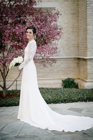 bride-in-long-sleeve-illusion-lace-wedding-dress-holding-white-bouquet-for-new-years-eve-wedding