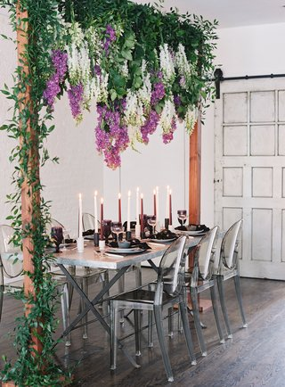 wedding-table-silver-ghost-chairs-tall-candles-wisteria-purple-white-greenery-wood-arch-industrial