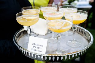 bride-signature-drink-peach-bellini-in-coupe-glass-fresh-peach-slices-on-tray-cocktail-hour