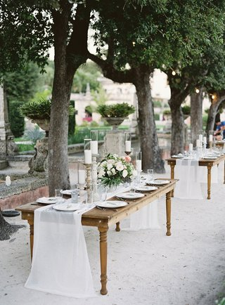 wedding-reception-tables-without-chairs-wood-white-linen-runner-candlesticks-neutral-flowers