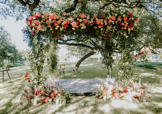outdoor-wedding-ceremony-austin-texas-greenery-pink-orange-coral-flowers-at-base-and-arch