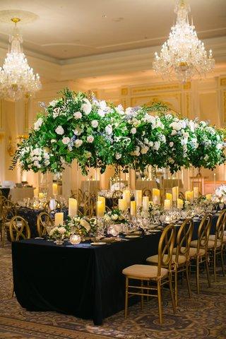 wedding-reception-ballroom-carpet-navy-blue-linen-gold-chairs-candles-tall-centerpieces-chandelier