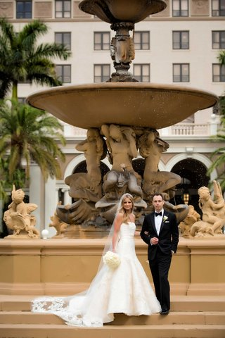 bride-in-strapless-wedding-dress-and-bouquet-with-cathedral-veil-and-groom-in-tux-at-the-breakers