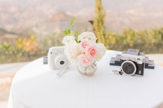 wedding-reception-white-linen-cocktail-table-with-pink-and-white-flower-bud-vase-instax-cameras
