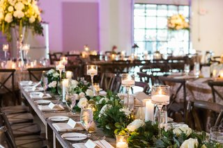 candlelight-and-tall-centerpieces-with-long-wooden-tables-and-greenery