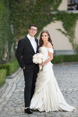 bride-in-off-the-shoulder-pnina-tornai-wedding-dress-and-groom-in-tuxedo-with-white-bow-tie-glasses