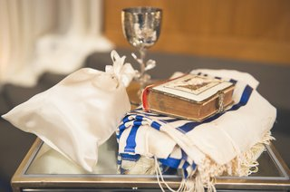 holy-book-white-tallit-with-blue-stripes-michael-aram-kiddush-cup-satin-bag-at-jewish-wedding