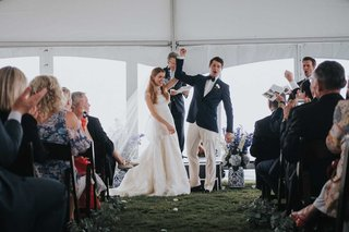 bride-and-groom-clasp-hands-and-raise-during-tented-wedding-ceremony-blue-white-vase-guests-clapping