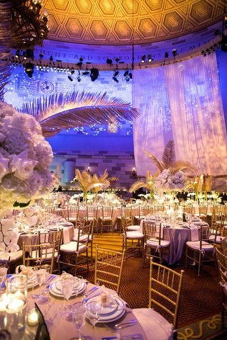 wedding-reception-gold-chairs-white-orchid-rose-hydrangea-centerpiece-gold-palm-leaves-purple-light