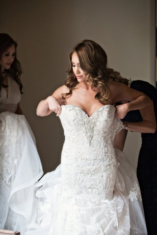bride-helped-into-kittychen-couture-lace-gown-with-beading-along-sweetheart-neckline