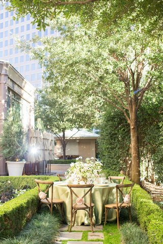 wooden-chairs-green-table-linens-low-full-floral-arrangement-greenery-alfresco-garden-city-setting
