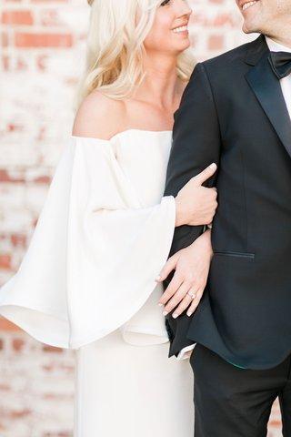 bride-wearing-bell-sleeves-and-groom-in-tuxedo