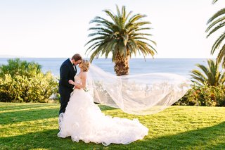 bride-in-demetrios-groom-in-ermenegildo-zegna-kiss-on-grass-ocean-view