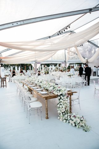 beach-wedding-with-a-clear-tent-draping-and-head-table-with-runner-of-white-pink-flowers-greenery