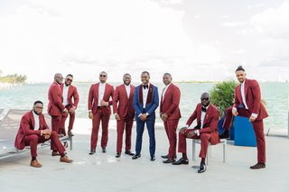 groom-in-navy-tuxedo-with-burgundy-lapels-groomsmen-in-maroon-suits