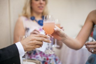 bride-to-be-passing-glass-of-peach-bellini-to-bridal-shower-guest