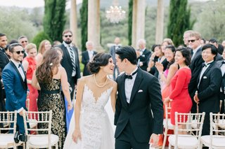 bride-and-groom-smile-at-each-other-during-outdoor-wedding-ceremony-guests-look-at-couple-chairs