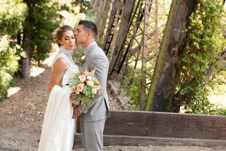 bride-in-ines-di-santo-wedding-dress-from-the-white-dress-high-neck-necklace-over-gown-bouquet-grey