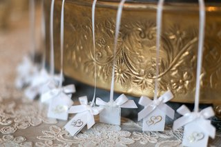 wedding-cake-pulls-on-white-ribbons-with-white-bows-labels-with-golden-hearts