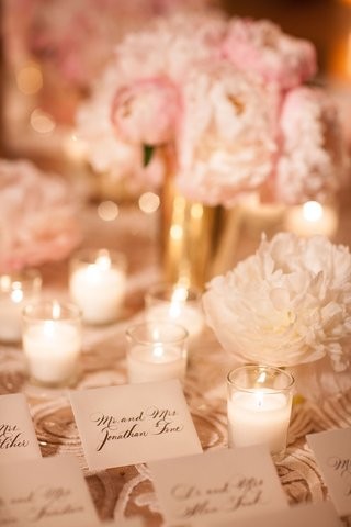 texture-linens-with-pink-peony-and-white-peony-flowers-candle-votives-gold-vases-escort-card-table