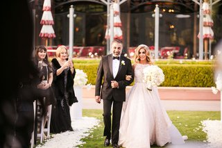 bride-in-high-neck-ball-gown-hayley-paige-walking-down-aisle-with-father-persian-wedding-outdoor