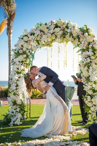 newlywed-couple-dip-kiss-outdoor-ceremony-flowers-garden-wedding-beach-floral-arch-slit-dress-ca