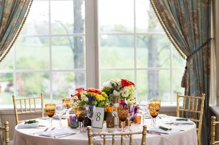 bright-colored-flowers-and-rustic-reception-decor-in-front-of-glass-windows-with-curtains