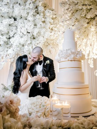bride-and-groom-kissing-with-glass-of-champagne-before-wedding-cake