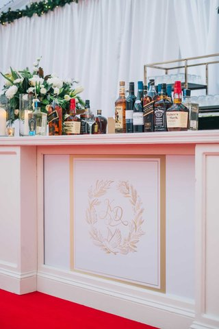 wedding-reception-bar-white-with-gold-monogram-red-carpet-greenery-white-flowers