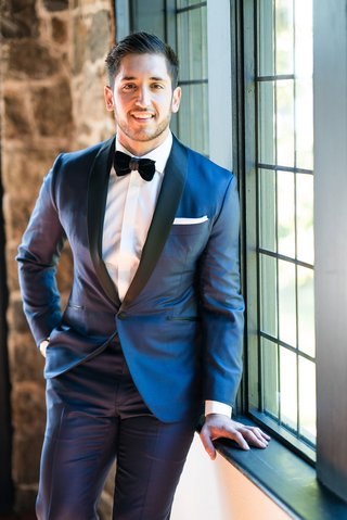 wedding-getting-ready-groom-in-navy-suit-with-black-lapels-and-velvet-bow-tie-white-cuffs-pocket