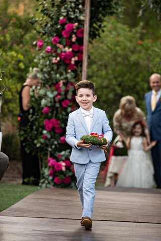 cute-ring-bearer-in-light-blue-suit-white-bow-tie-moss-ring-pillow-wood-aisle-pink-flowers