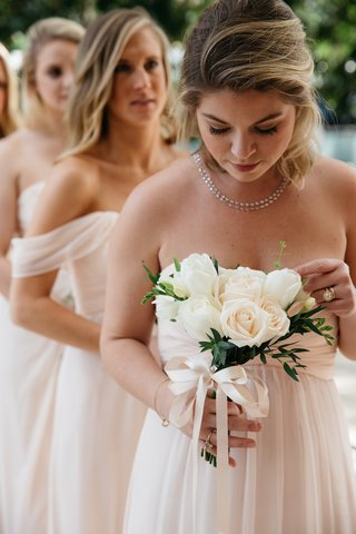 bridesmaid-in-a-light-amsale-dress-holds-bouquet-of-white-roses-and-tulips-greenery