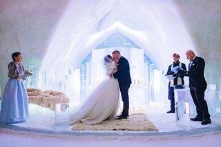 bride-and-groom-kiss-ice-castle-wedding-ceremony-fur-rug-ice-altar-pews-unique-wedding-venue