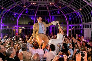 bride-and-groom-on-chairs-in-crowd-at-purple-wedding-reception