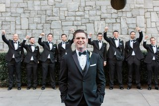 groom-in-tuxedo-and-bow-tie-with-cheering-groomsmen-behind-him