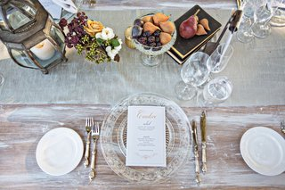 whitewash-wood-table-with-crystal-charger-personalized-menu-card-calligraphy-and-low-centerpieces